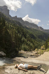Woman lying on a rock in the mountains, Ordesa national park, Aragon, Spain - AHSF00854