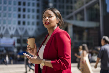 Portrait of businesswoman with coffee to go and cell phone, London, UK - MAUF02942