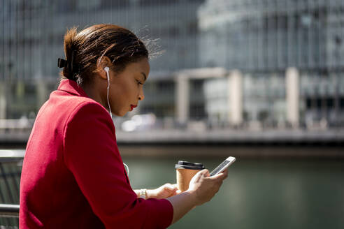 Profile of businesswoman with coffee to go using mobile phone and earbuds, London, UK - MAUF02945