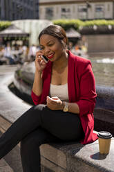Portrait of smiling businesswoman on the phone, London, UK - MAUF02948