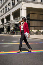 Businesswoman drinking coffee to go while crossing the street on LGBT stripes, London, UK - MAUF02957
