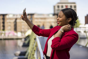 Smiling businesswoman standing on bridge taking selfie with smartphone, London, UK - MAUF02963