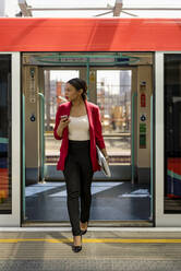 Businesswoman with cell phone getting out off the train, London, UK - MAUF02966