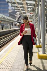 Smiling businesswoman walking on platform looking at mobile phone, London, UK - MAUF02969