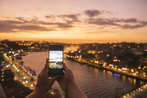Woman's hands holding smartphone with a photo of panoramic view of Porto at sunset, Portugal - AHSF00871