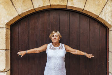 Portrait of a senior woman in front of a wooden door - MOSF00018