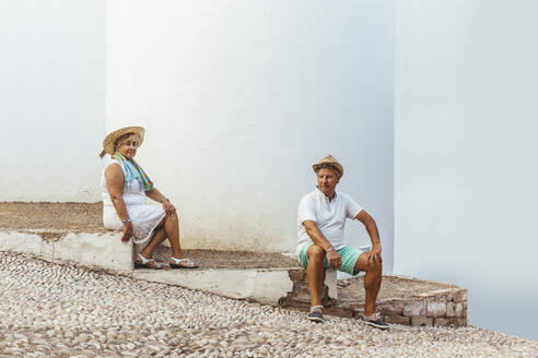 Senior tourist couple sitting on steps in a village, El Roc de Sant Gaieta, Spain - MOSF00021