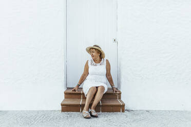 Senior tourist sitting on stoop in a village, El Roc de Sant Gaieta, Spain - MOSF00024