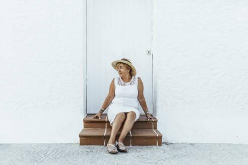 Senior tourist sitting on stoop in a village, El Roc de Sant Gaieta, Spain - MOSF00024