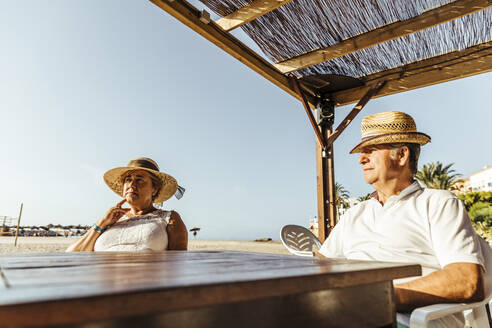 Senior couple sitting at a bar terrace at the beach, El Roc de Sant Gaieta, Spain - MOSF00027