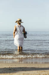 Senior woman wading in the sea, El Roc de Sant Gaieta, Spain - MOSF00033