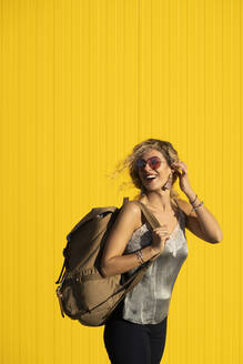 Portrait of young woman with backpack in front of yellow background - DAMF00142