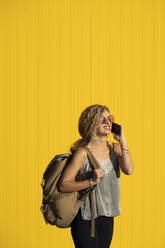Young woman on the phone  in front of yellow background - DAMF00145