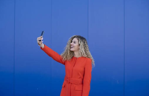 Smiling young woman wearing red dress taking selfie in front of blue background - DAMF00154
