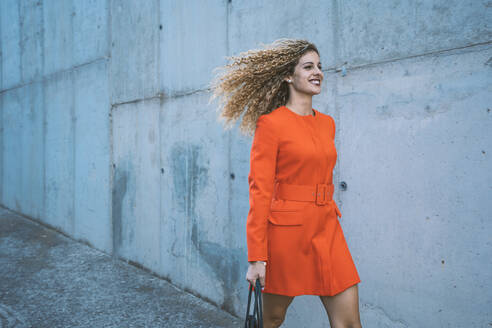 Happy young woman wearing red dress walking along street - DAMF00157