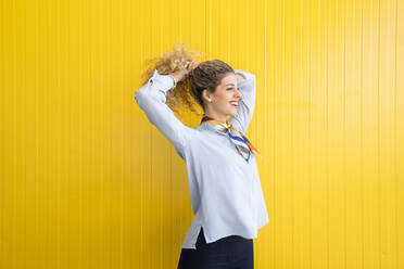 Smiling young woman tying her hair in front of yellow background - DAMF00160
