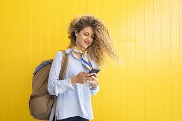 Smiling young woman with backpack in front of yellow background looking at cell phone - DAMF00163