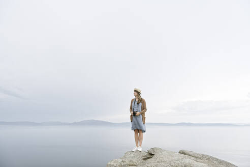 Woman with camera  standing on rock, looking at the sea - AHSF00878