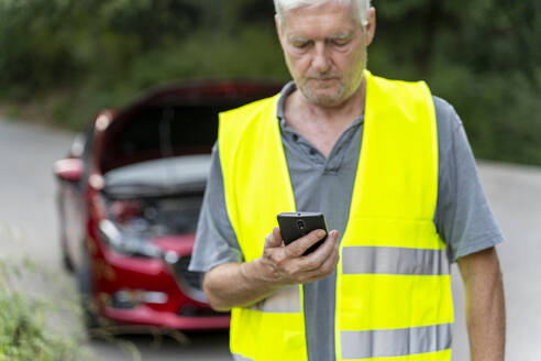 Senior man standing at his broken car wearing a safety vest and using his smartphone - AFVF04058