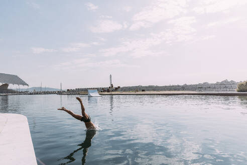 Young man jumping into water from a pier - MOSF00046