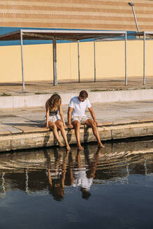 Young couple sitting on a pier at the sea - MOSF00064