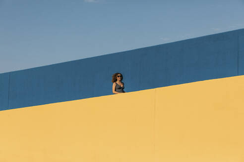 Young woman behind a yellow wall - MOSF00067