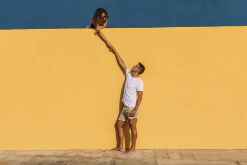 Young man and woman behind a yellow wall holding hands - MOSF00070