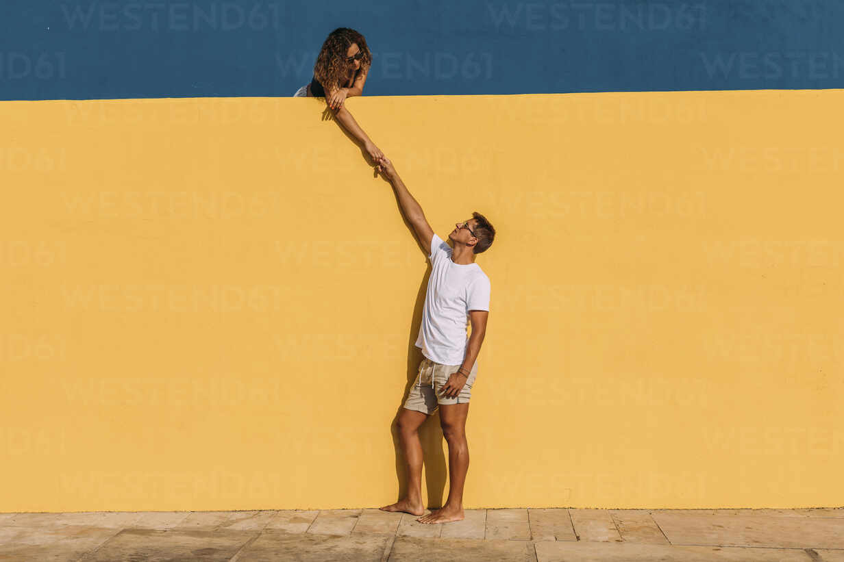 Young man and woman behind a yellow wall holding hands - MOSF00070 - Marcos Osorio/Westend61