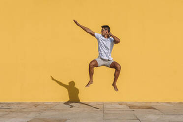 Young man jumping in front of a yellow wall - MOSF00076