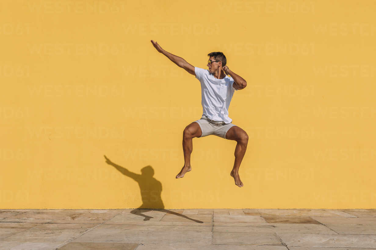Young man jumping in front of a yellow wall - MOSF00076 - Marcos Osorio/Westend61