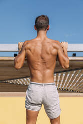 Rear view of athletic young man in shorts - MOSF00079
