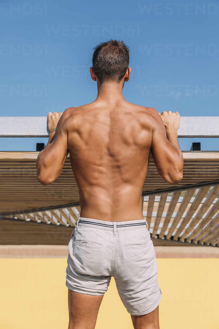 Rear view of athletic young man in shorts - MOSF00079 - Marcos Osorio/Westend61