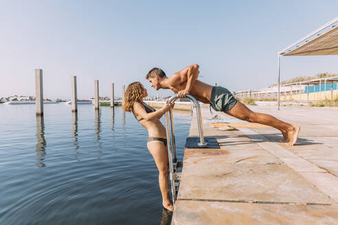 Young couple on a pier at the sea - MOSF00082