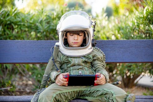 Boy wearing a space suit and sitting on a bench, playing alone with video games - CJMF00124