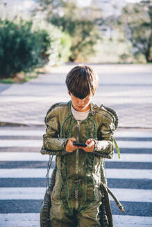 Boy wearing a space suit, crossing road and using smartphone - CJMF00127