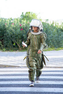 Boy wearing a space suit, crossing road and using smartphone - CJMF00130