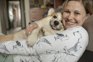 Portrait of happy woman cuddling with her dog at home - VPIF01601
