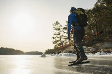 Man ice-skating on frozen lake - JOHF03023
