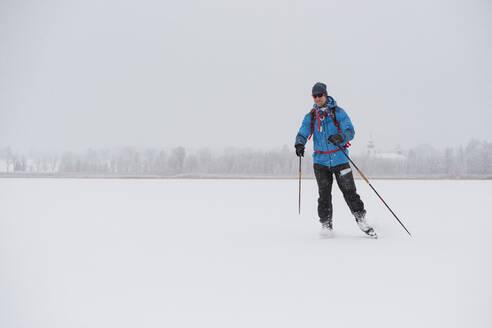 Man ice-skating on frozen lake - JOHF03026