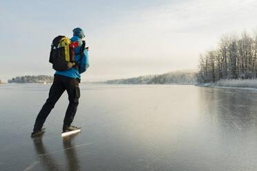 Man ice-skating on frozen lake - JOHF03029