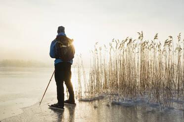 Man ice-skating on frozen lake - JOHF03032