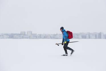 Man ice-skating on frozen lake - JOHF03038