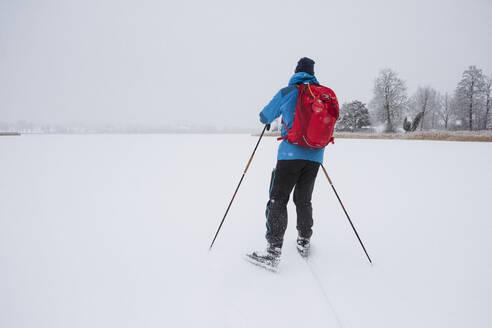 Man ice-skating on frozen lake - JOHF03041