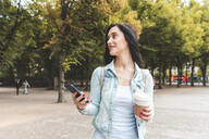 Young woman having a coffee and walking at a park, Berlin, Germany - WPEF02040