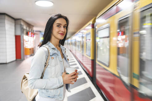 Young woman at metro station waiting for the train, Berlin, Germany - WPEF02043