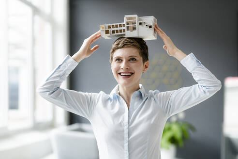 Happy businesswoman carrying architectural model on her head - KNSF06743