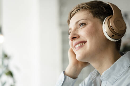 Portrait of happy businesswoman listening to music with headphones - KNSF06749