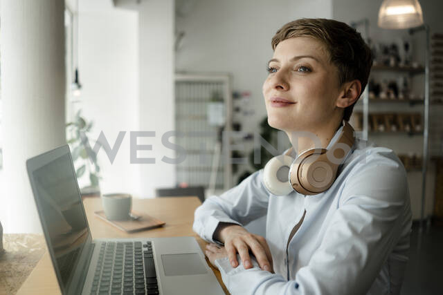 Businesswoman with laptop and headphones in a cafe - KNSF06752 - Kniel Synnatzschke/Westend61