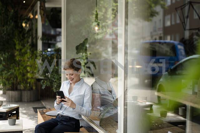 Businesswoman using cell phone at a cafe - KNSF06758 - Kniel Synnatzschke/Westend61