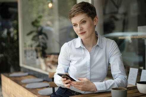 Daydreamining businesswoman with cell phone at a cafe - KNSF06761